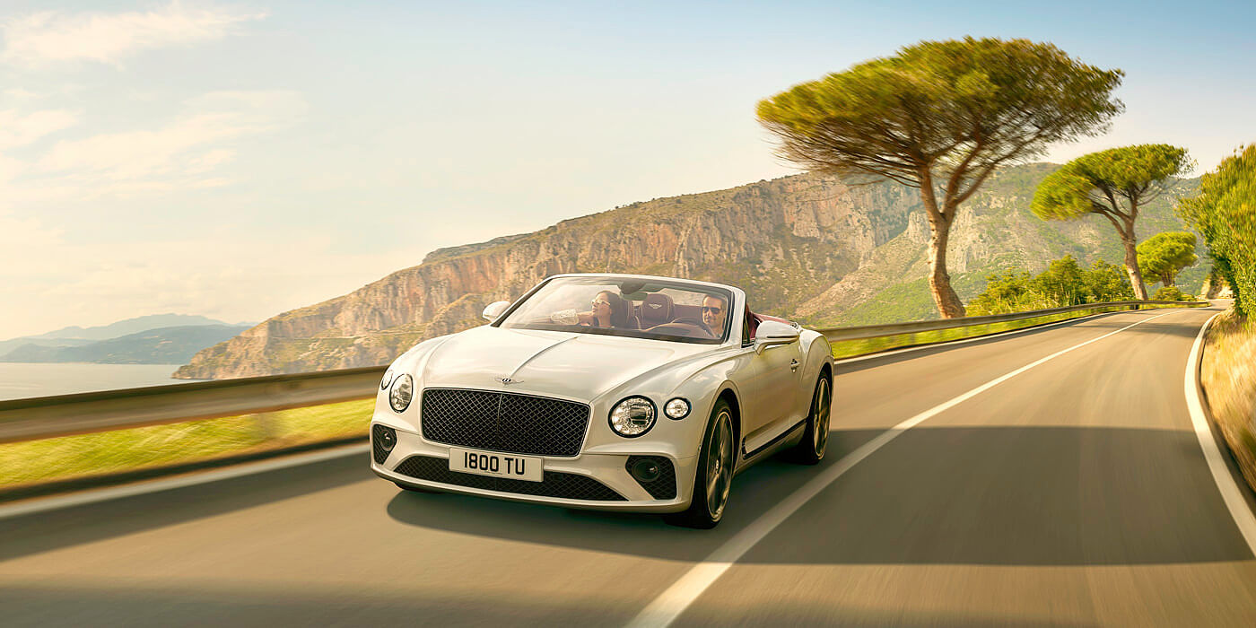 NEW-ICE-WHITE--BENTLEY-CONTINENTAL-GT-CONVERTIBLE-DRIVING-ON-MOUNTAIN-ROAD-BY-SEA